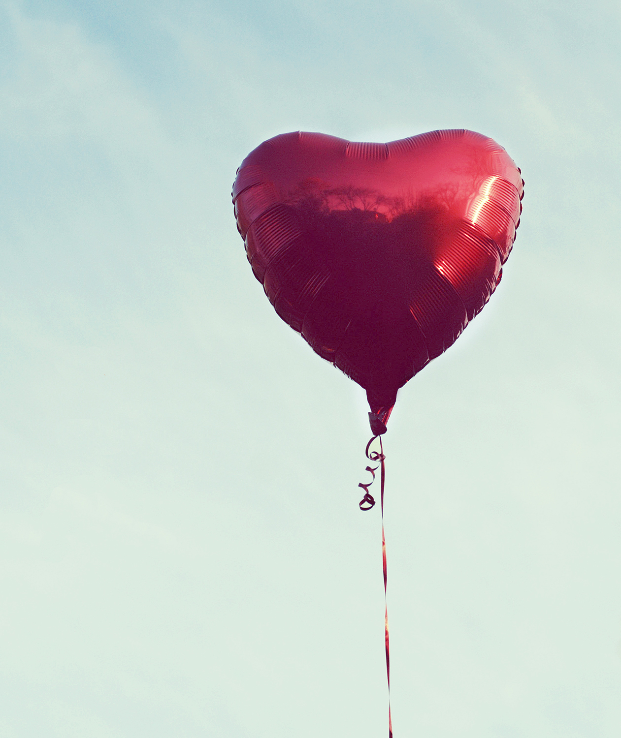 Red heart balloon against blue sky