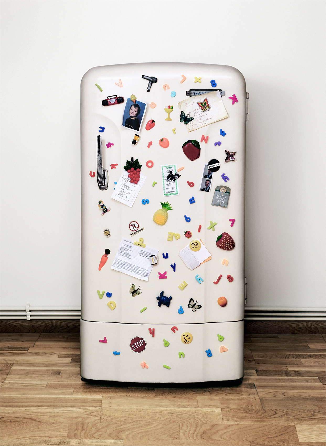 Refrigerator covered in magnets, notes, and photographs