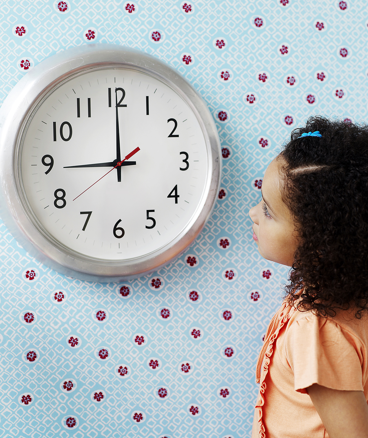 Little girl clooking at clock