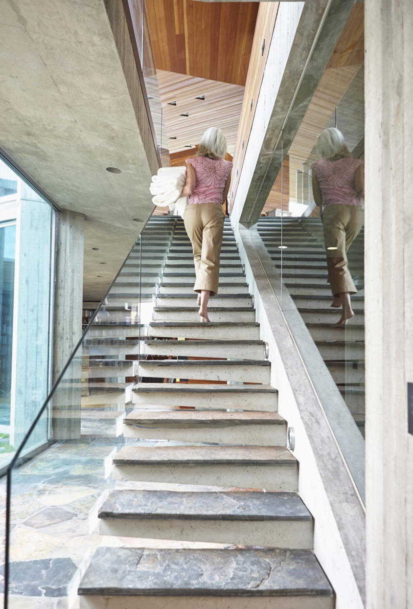Older Caucasian woman carrying laundry on modern staircase