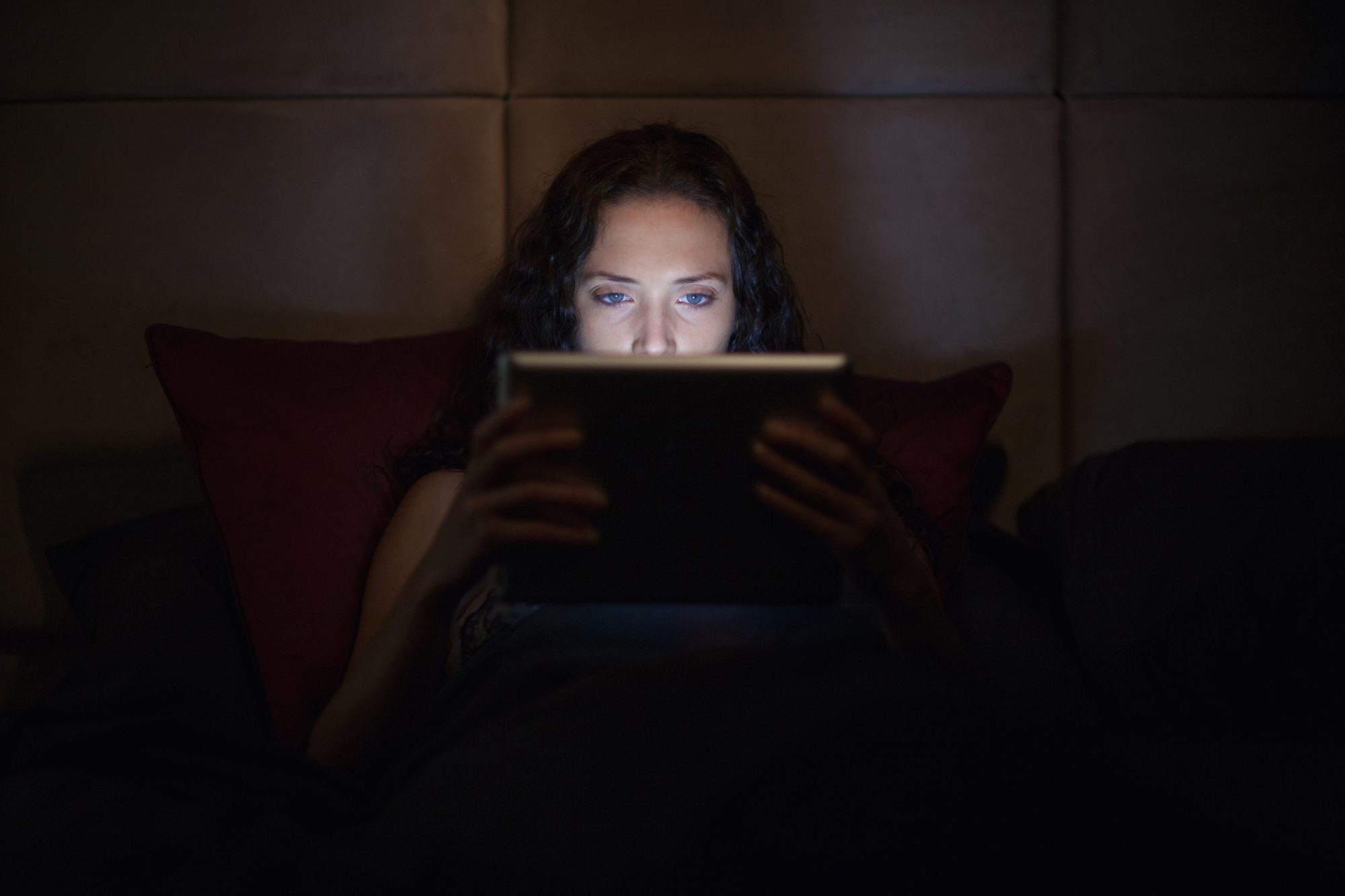 Woman reading tablet in bed