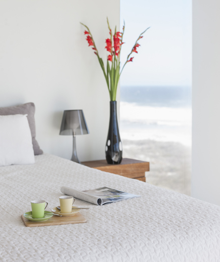 White hotel room with coffee, flowers