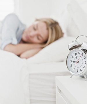 Woman sleeping next to an alarm clock on bedside table