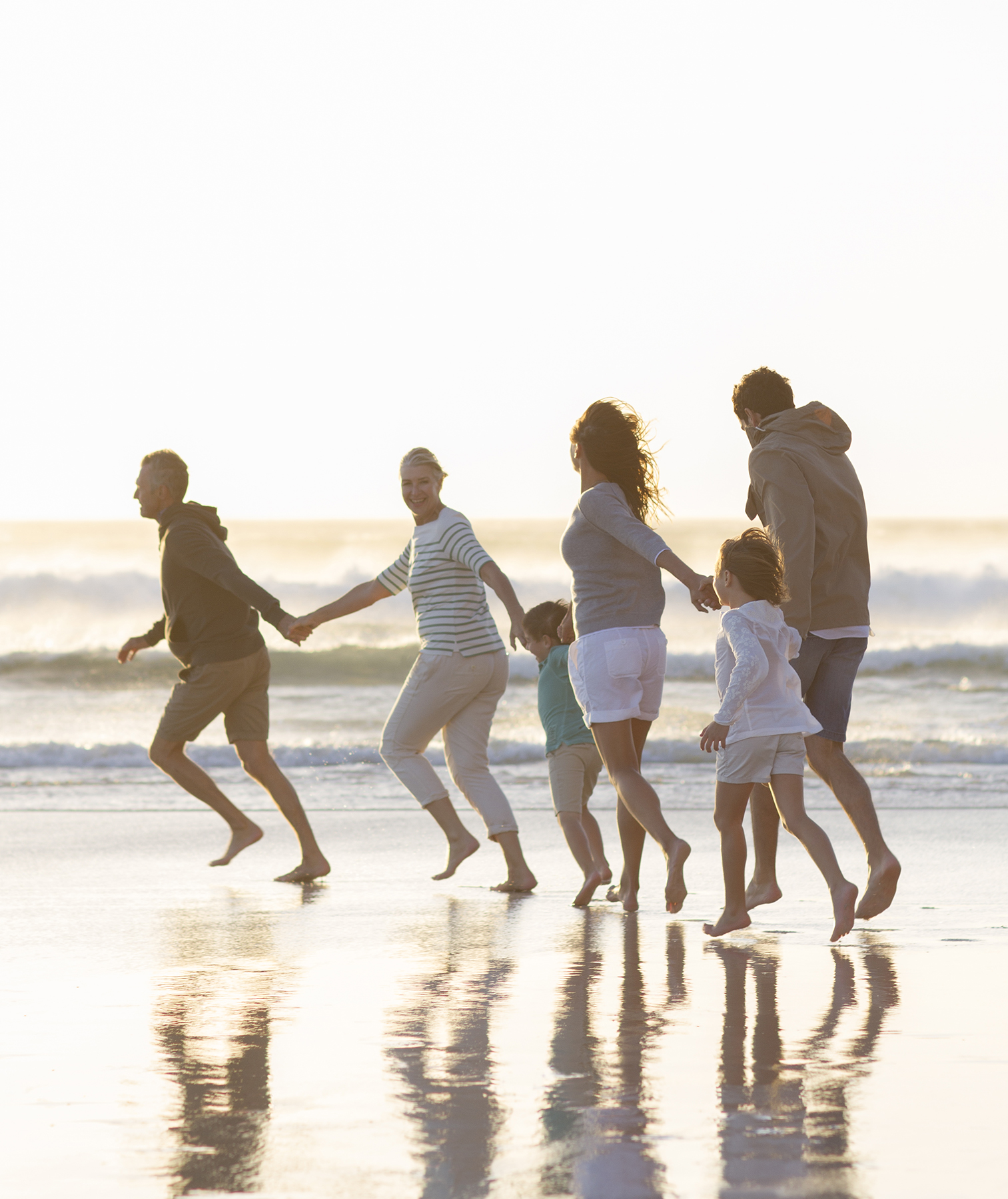 Extended family running on beach holding hands