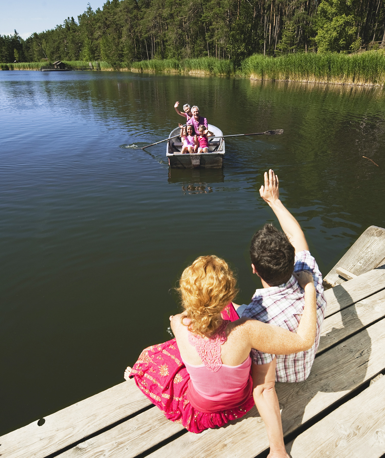 Couple waving at family on lake