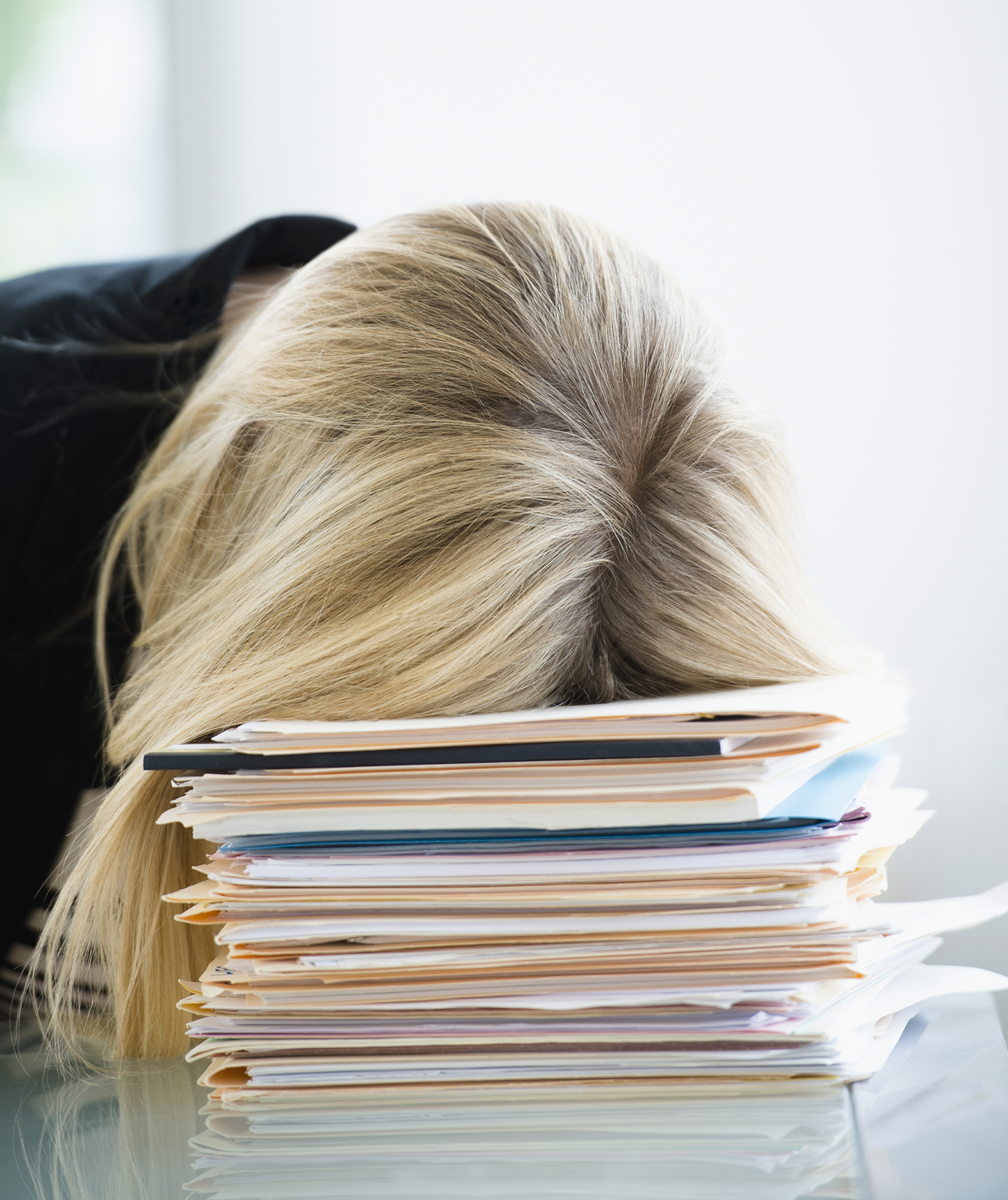 Woman sleeping on stack of files