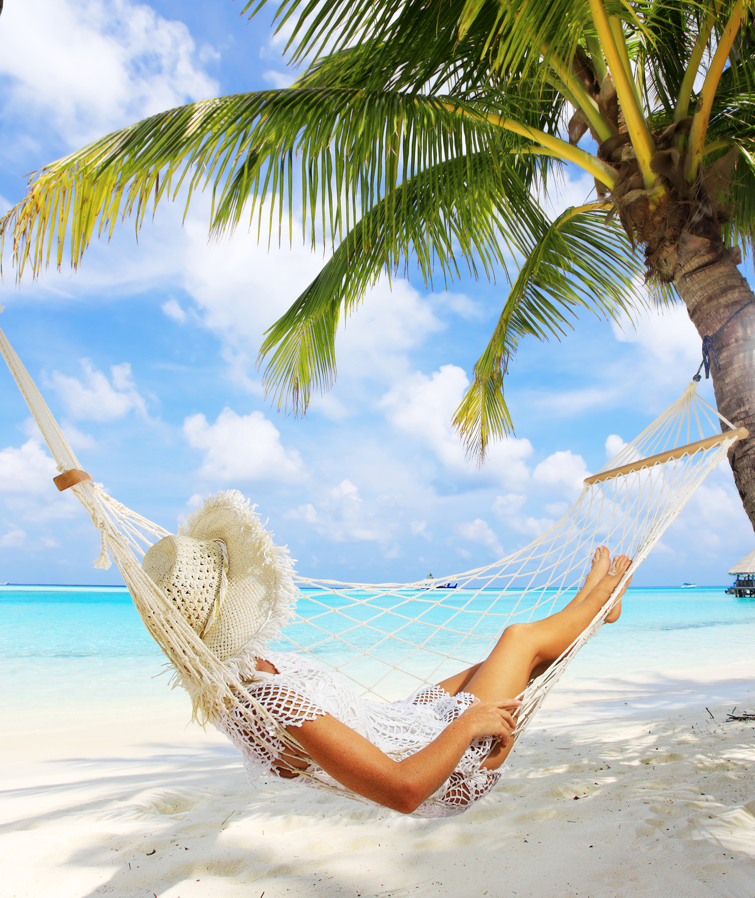 Woman in beach hammock between palm trees