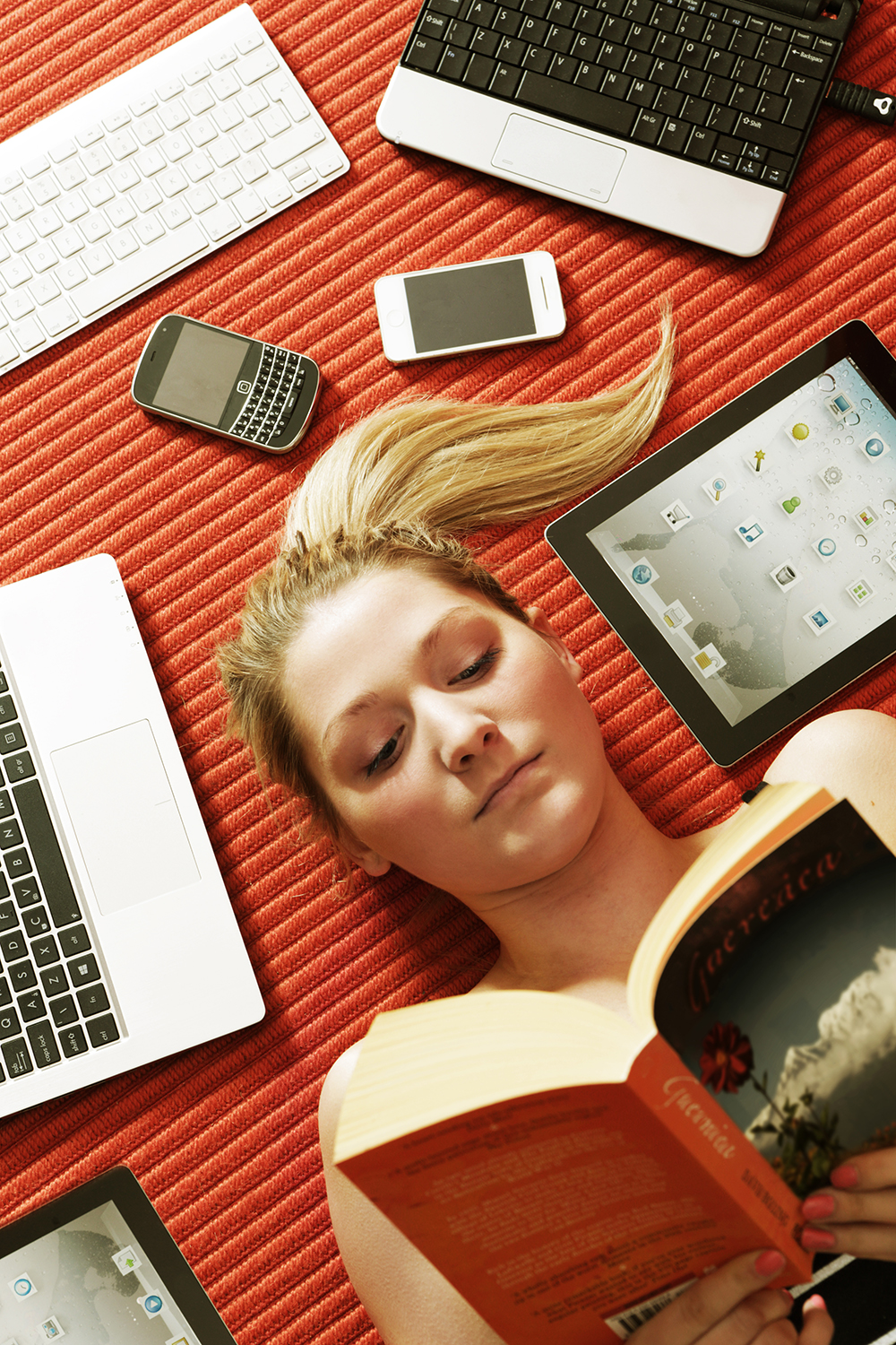 Woman reading book surrounded by technology