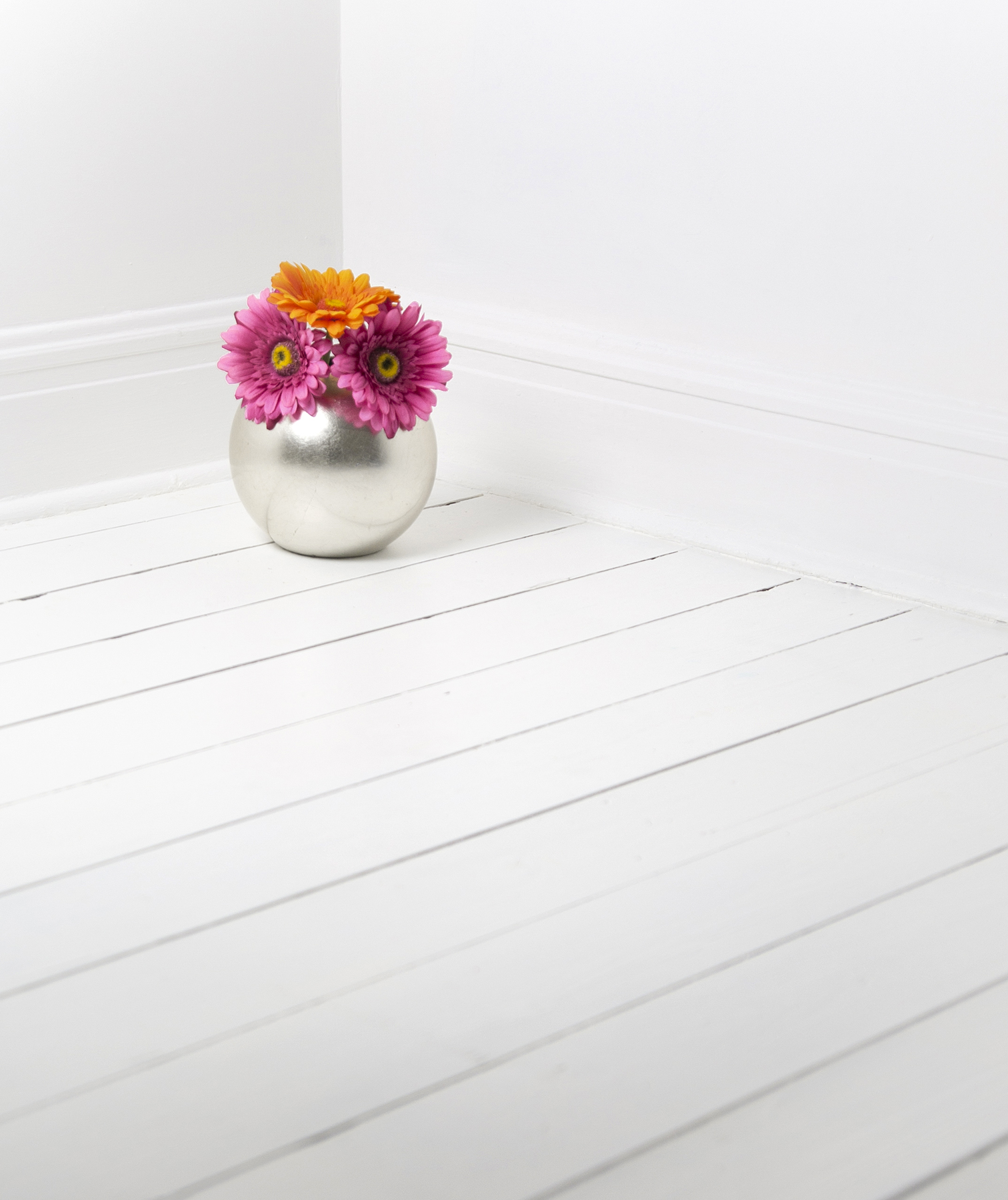 Vase of flowers on a white painted floor