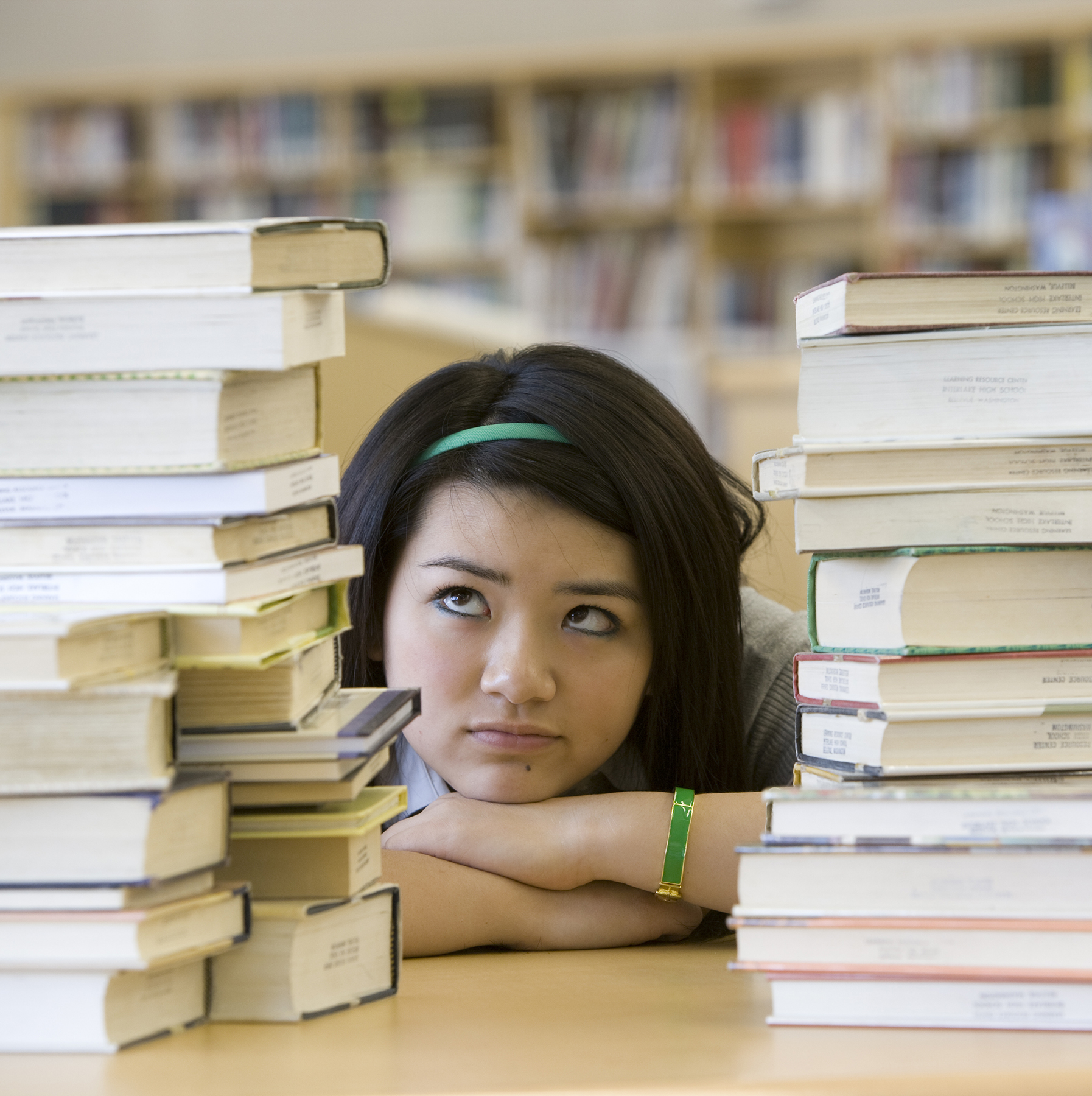 Teenager with stacks of books