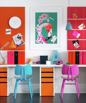 brightly colored home office space with flamingo print on wall