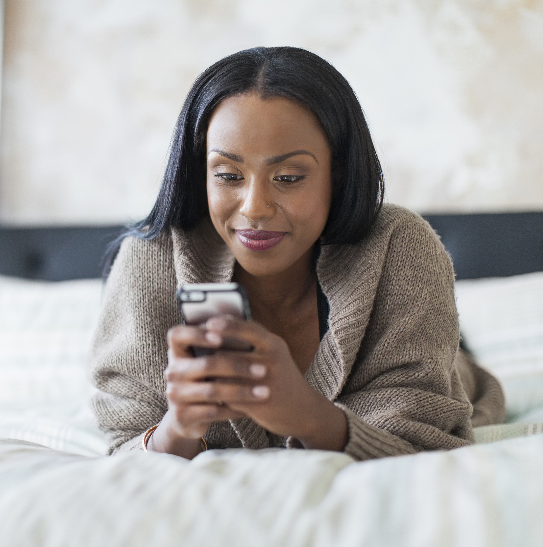 Woman texting on her bed