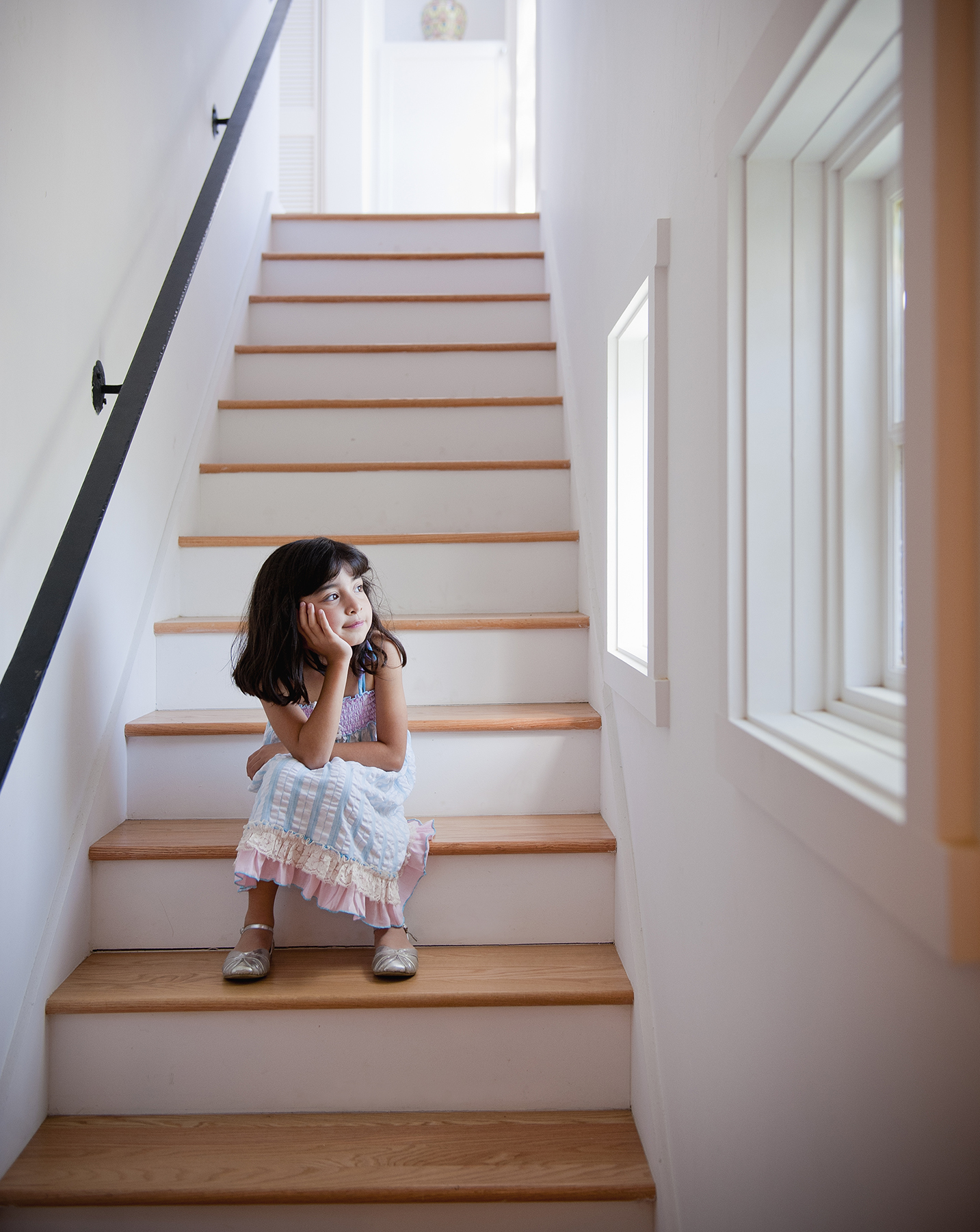 Girl sitting on the stairs looking out window