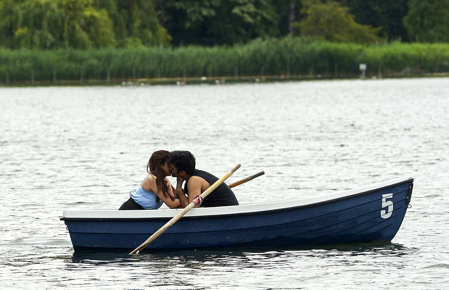 A couple kiss on a boat on the Serpentine in London's Hyde Park.