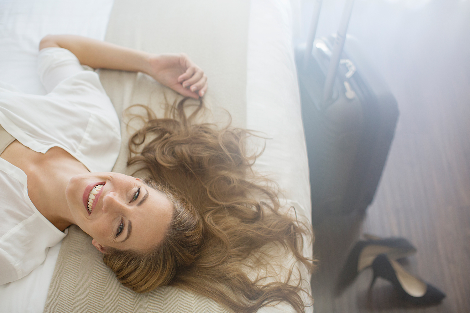 Woman Lounging on Bed Smiling