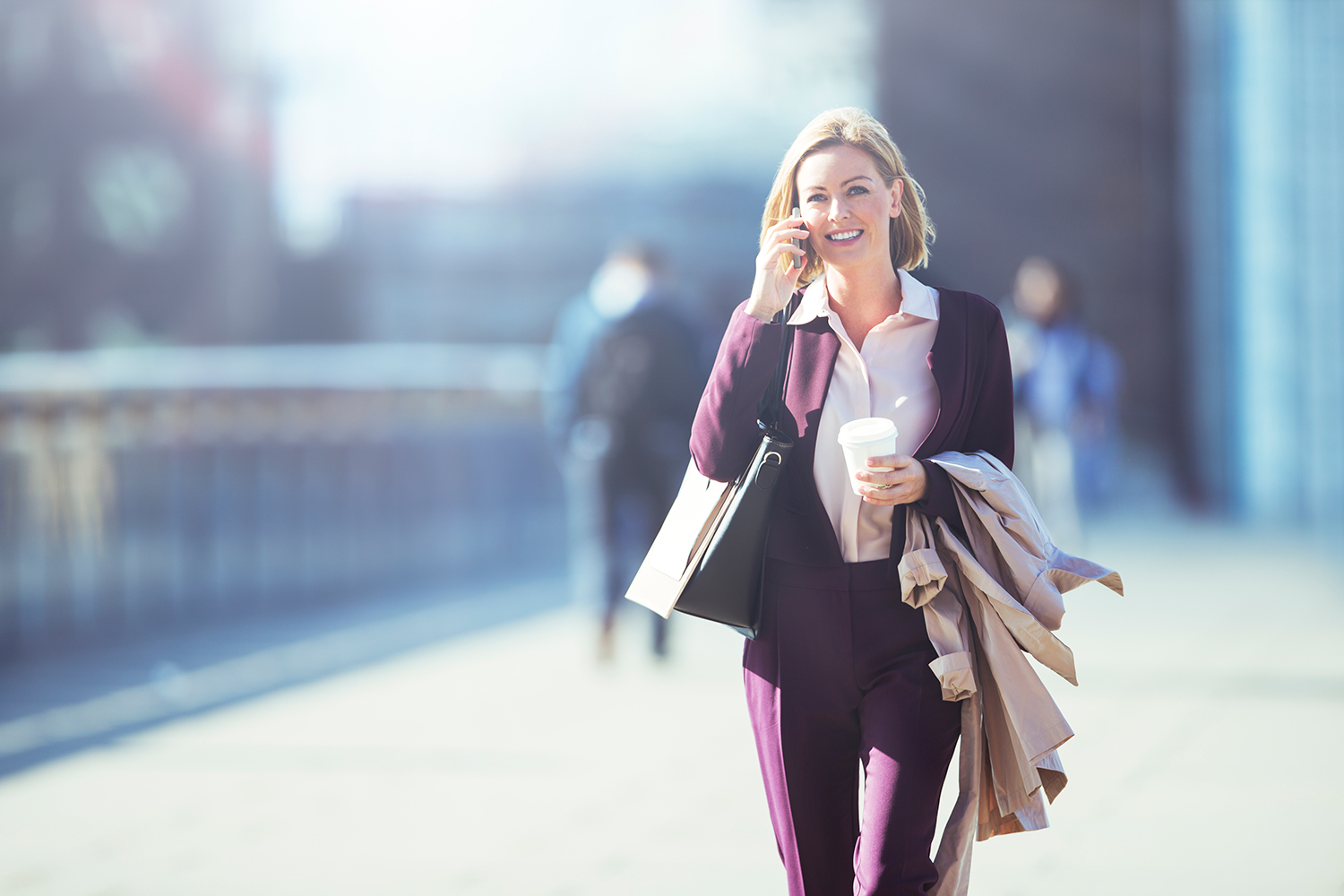 Woman Smiling While Walking Down the Street