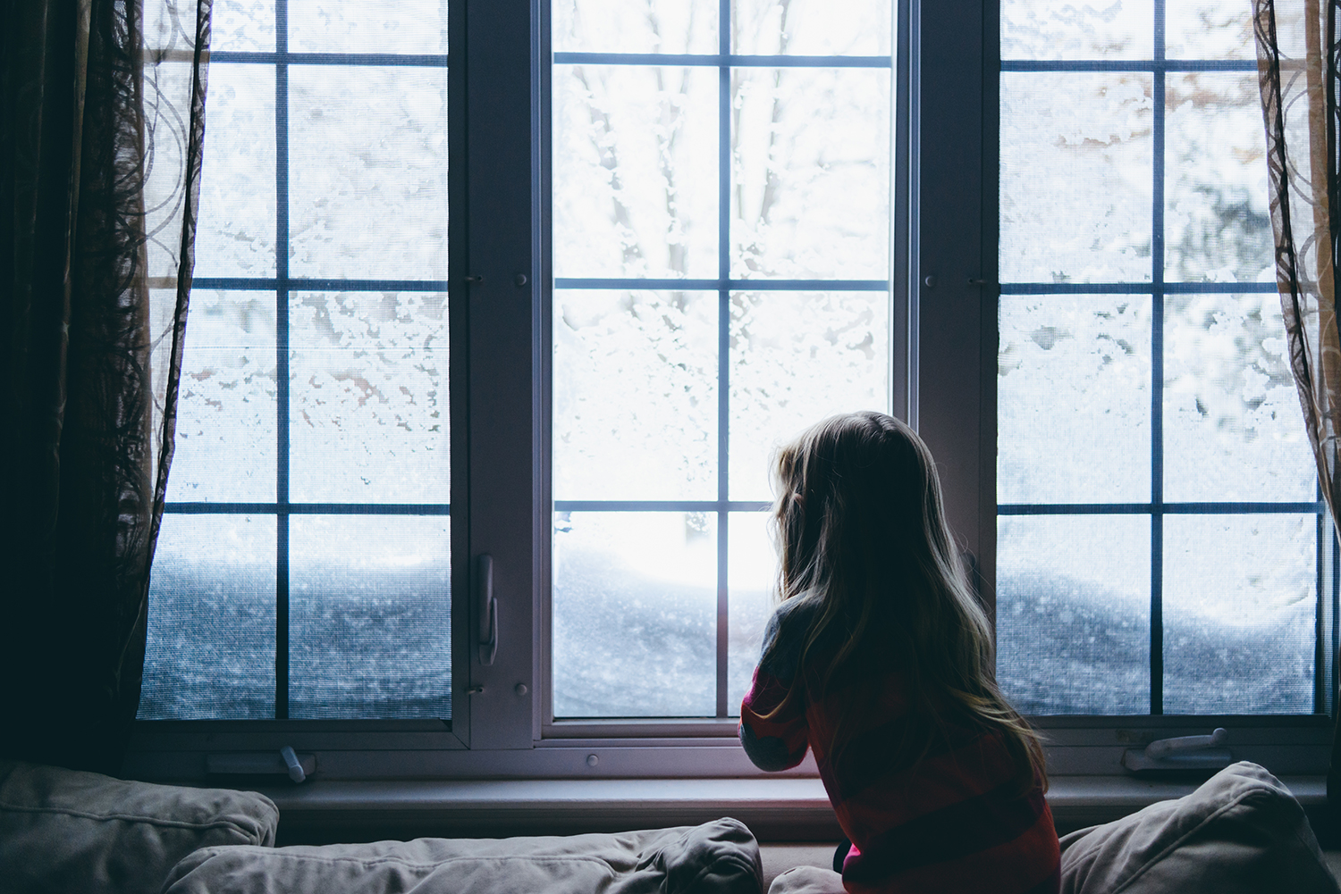 Girl Looking at Snow Through the Window of House