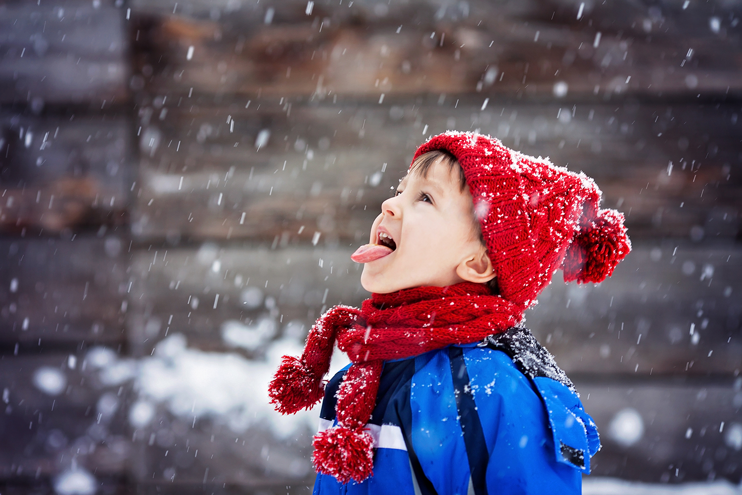 Child Catching Snow and Wearing a Red Hat