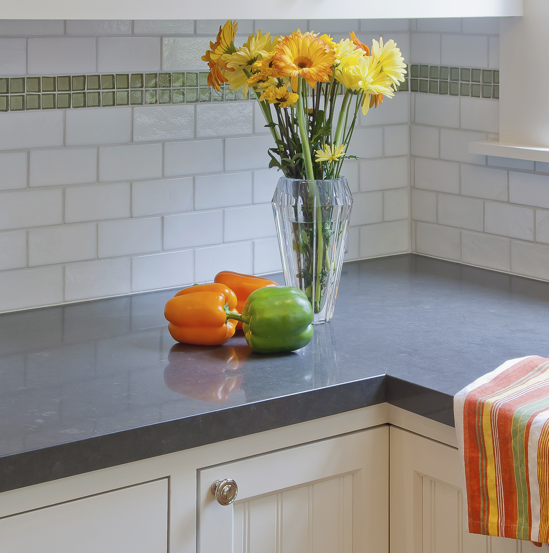 Counter with flowers and tile backsplash