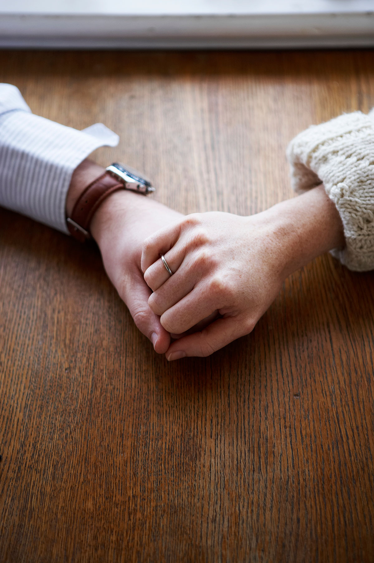 couple-holding-hands-on-table