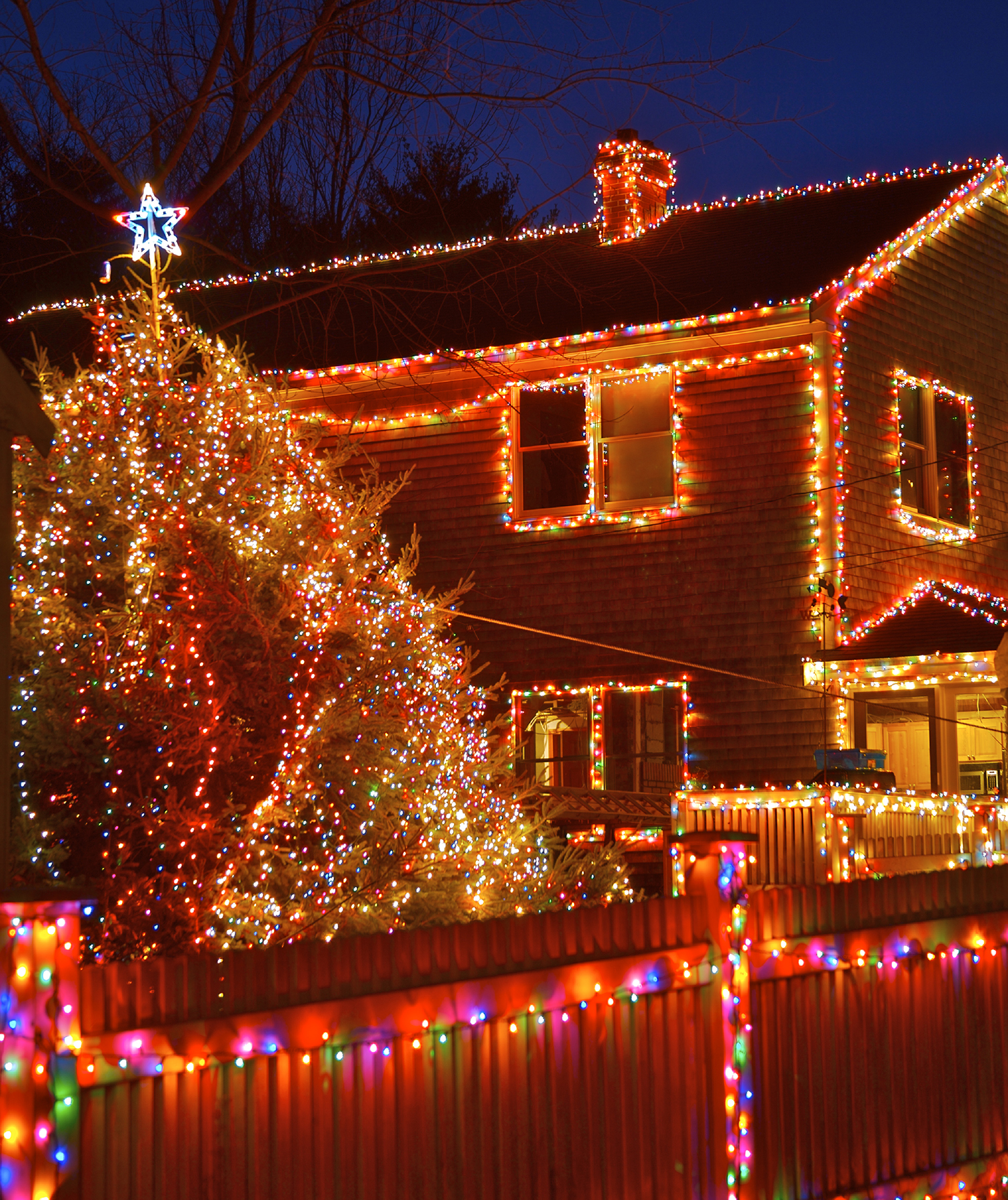 House, fence, trees covered with Christmas lights