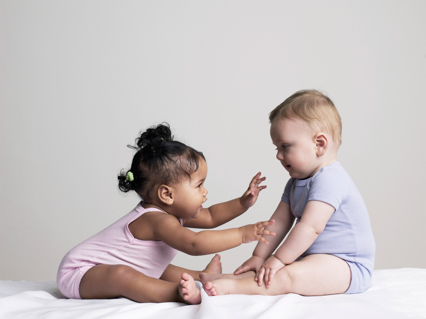 Baby girl and boy playing