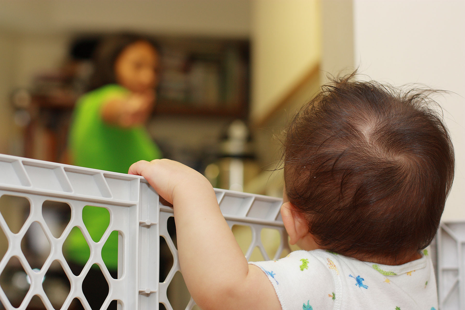 Baby Peering Over a Safety Gate