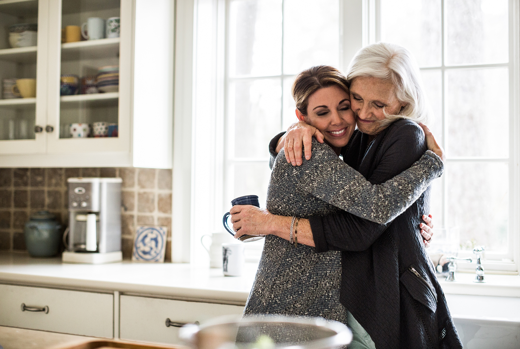 Senior mother hugging daughter in kitchen