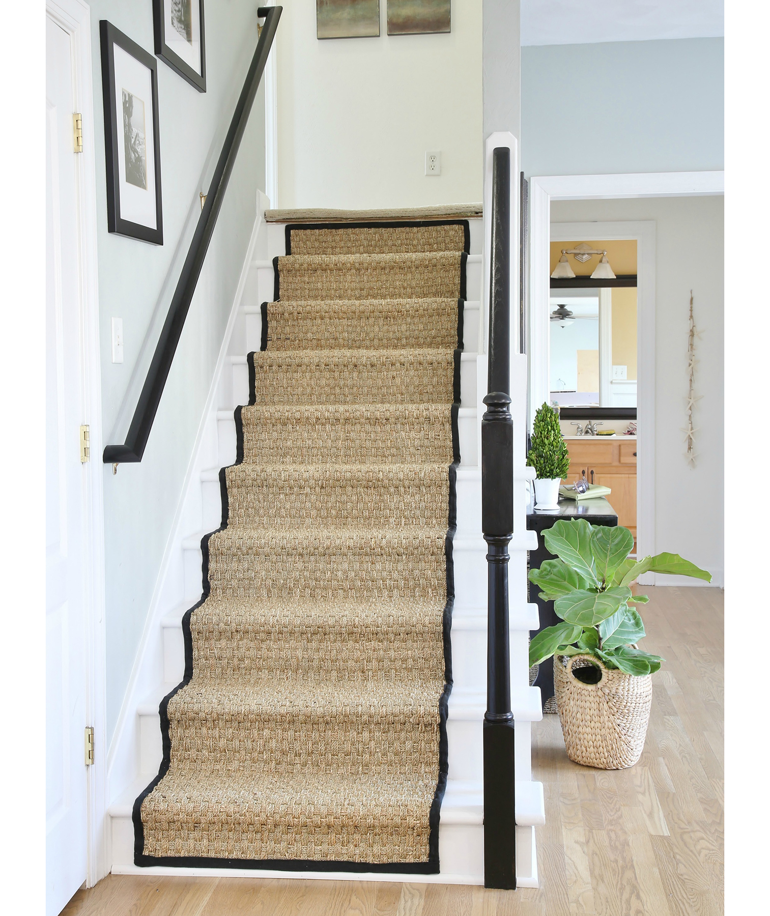 White staircase with seagrass runner