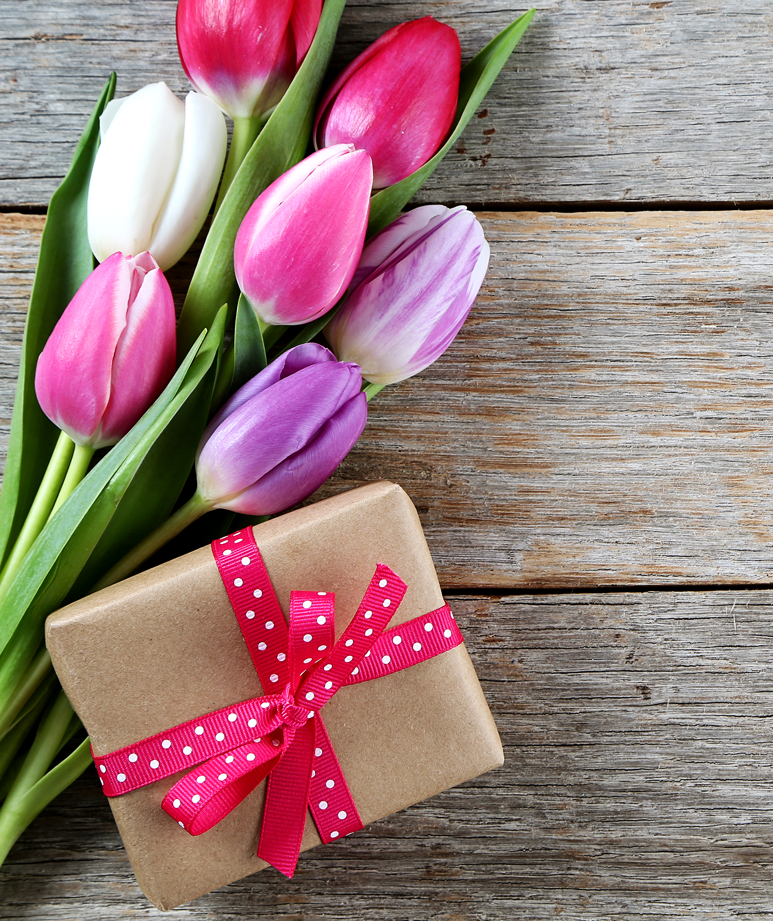 Gift and tulips on wood