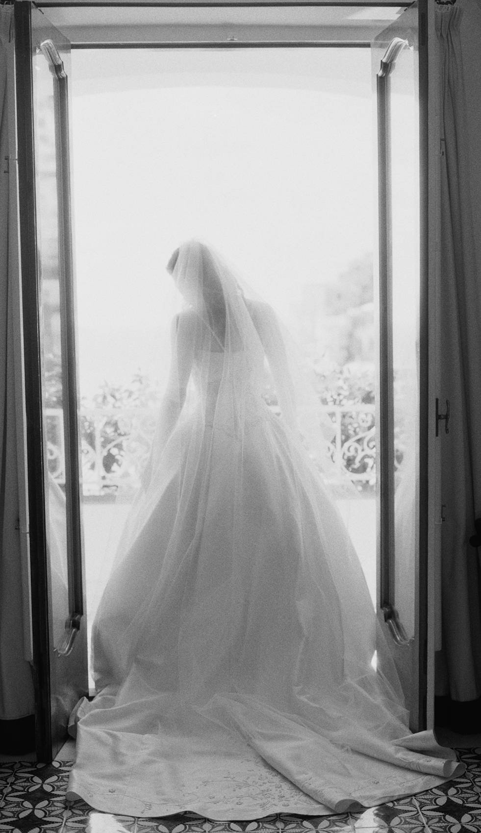 Bride wearing wedding gown and standing in doorway
