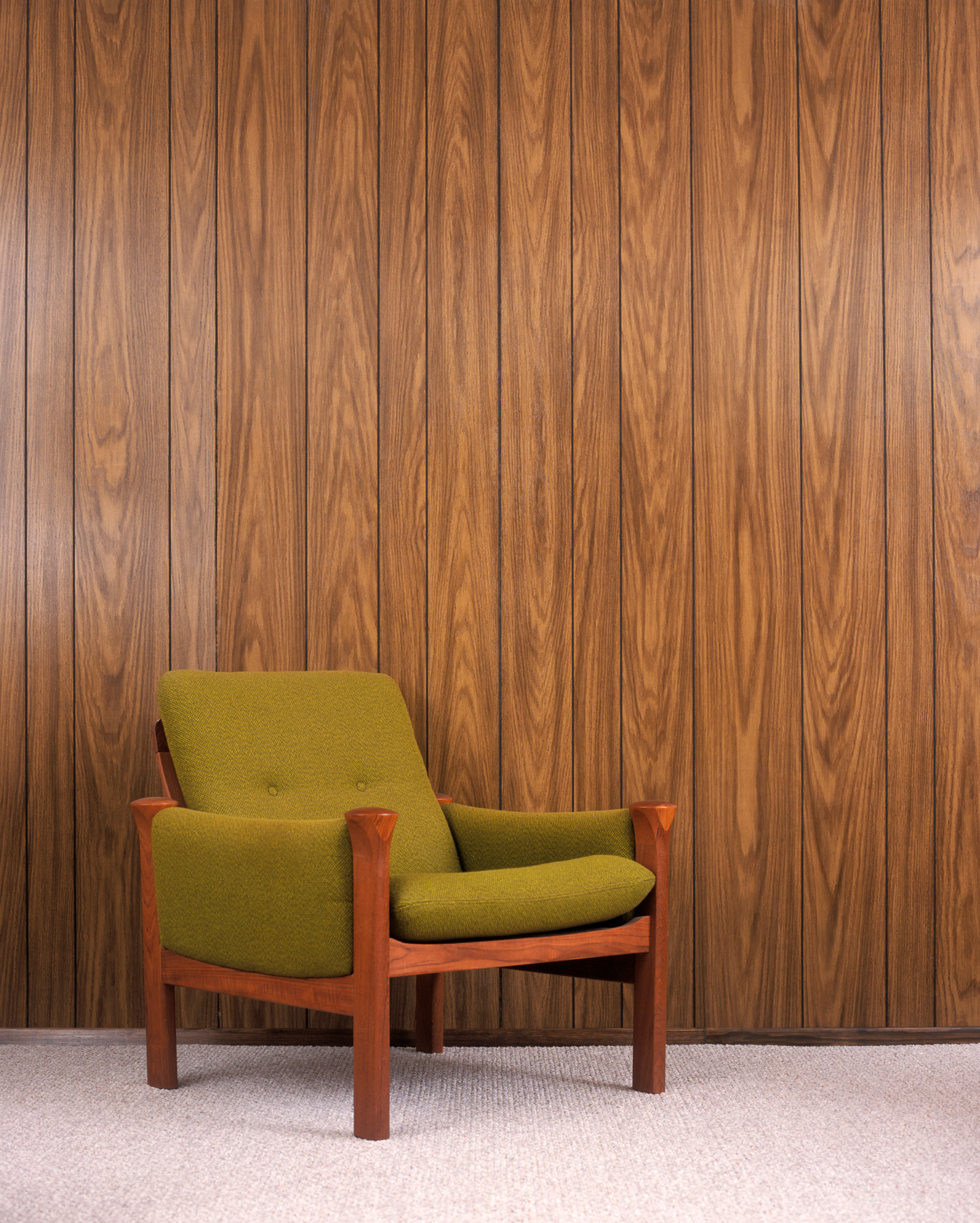 Chair in front of wood paneling