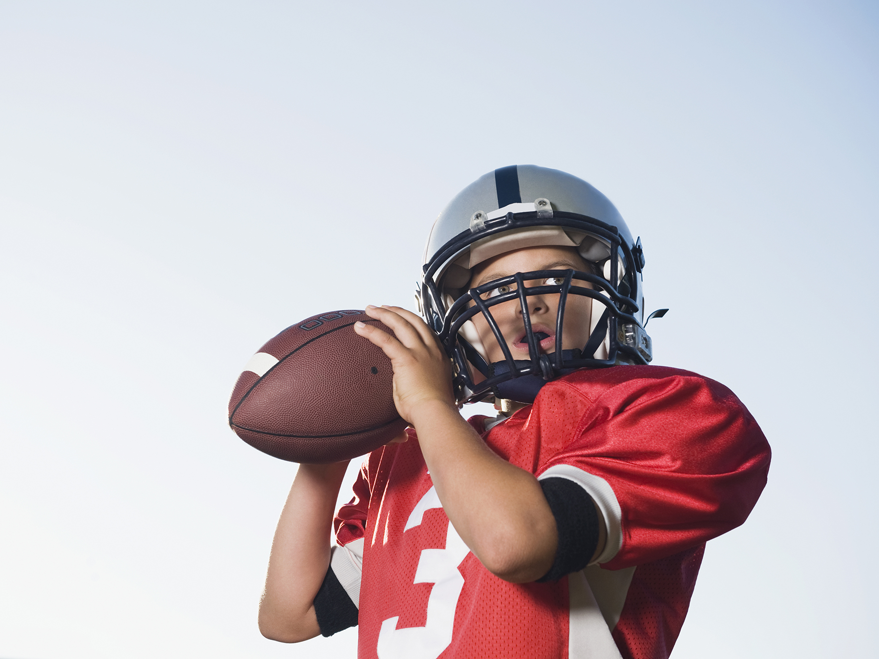 Boy playing football in uniform