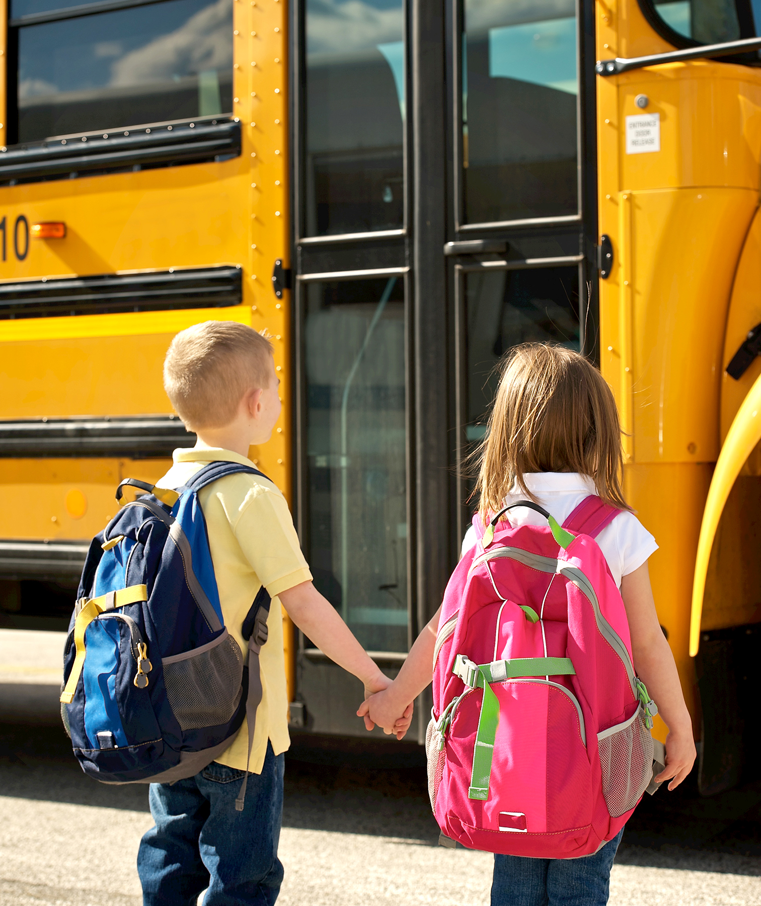 Kids holding hands in front of school bus