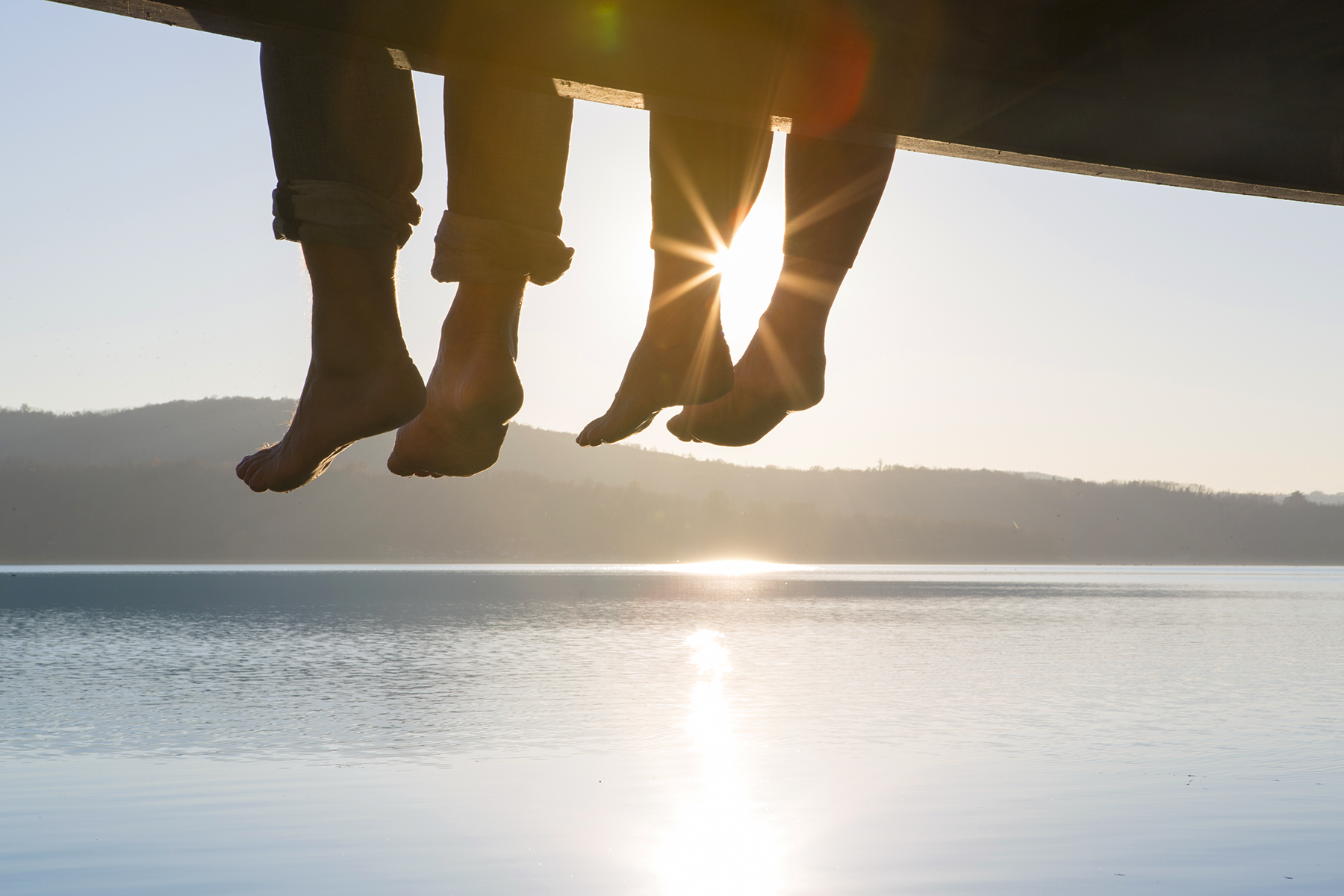 Couple with legs hanging off pier