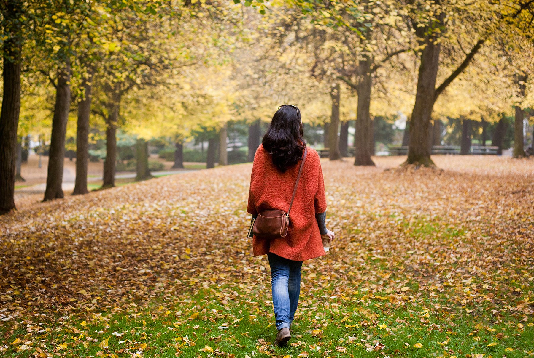 Woman walking through fall trees