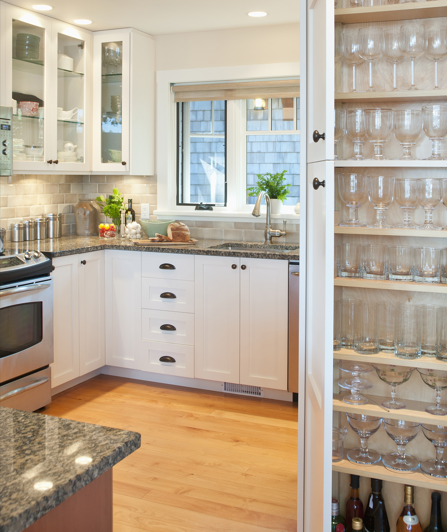 Kitchen with white drawers and wood floor