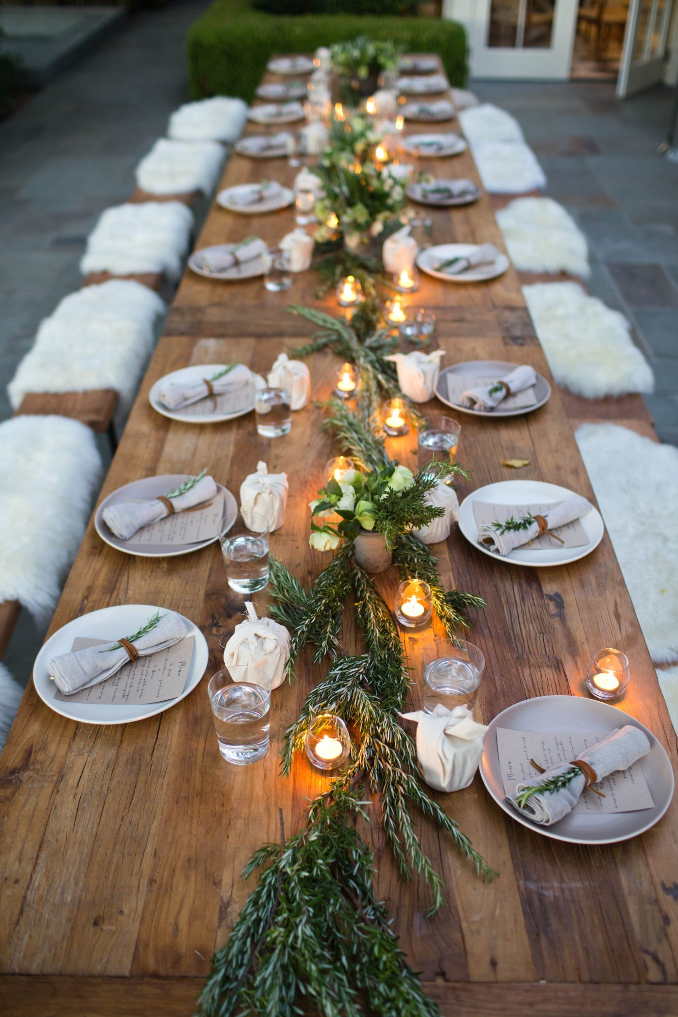 Long wood Thanksgiving table with fur-accented seating & 44 Thanksgiving Table Settings for 2017