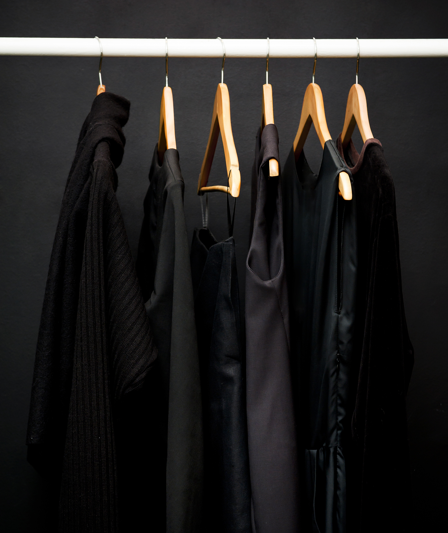 Black clothes hanging in black closet