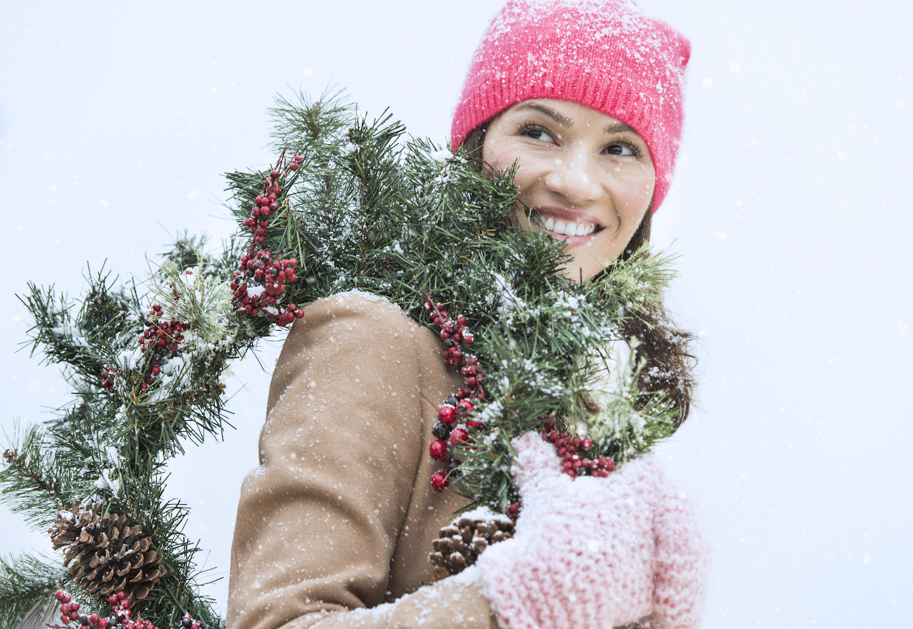 Woman carrying wreath in snow