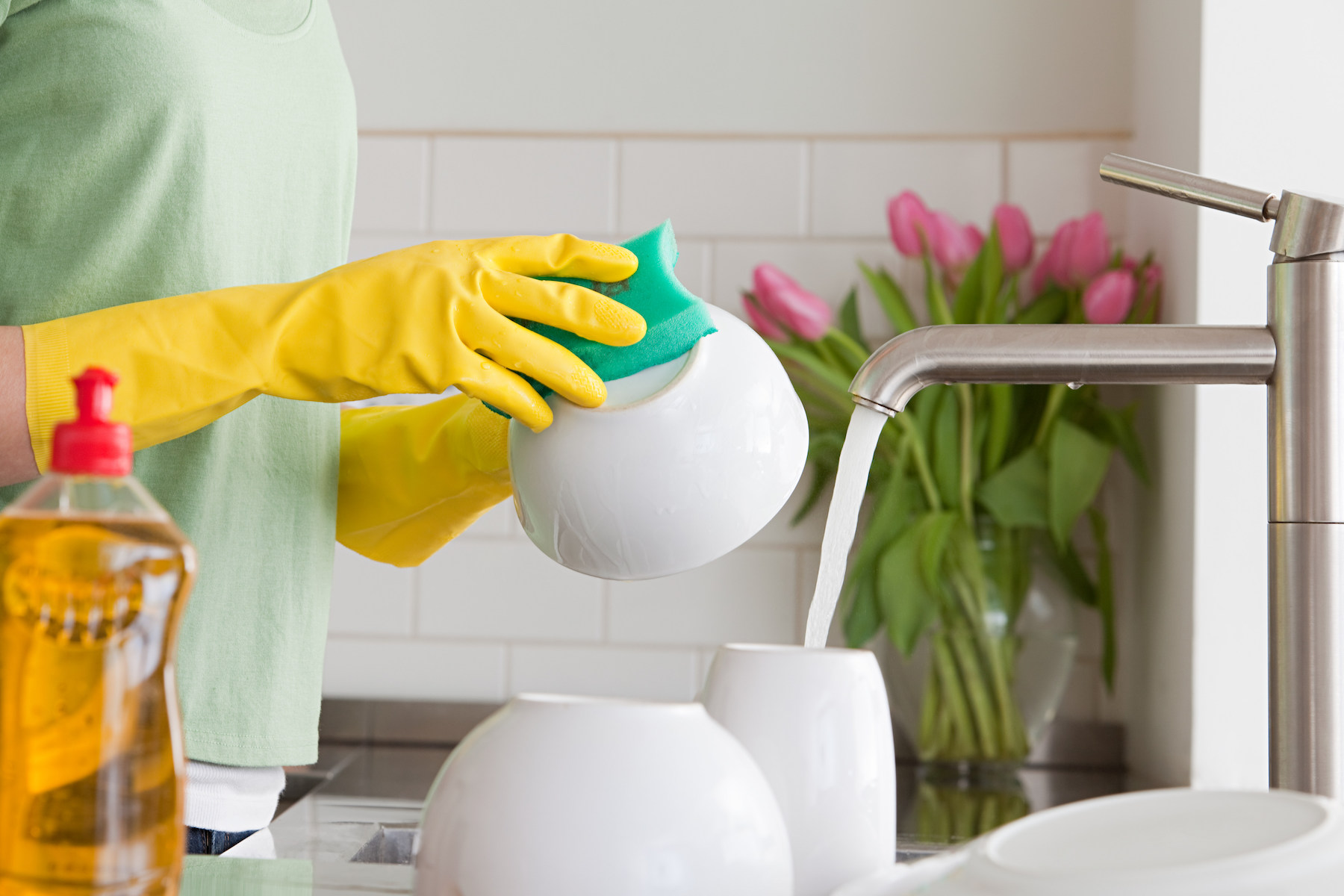 Woman washing dishes with sponge and flowers