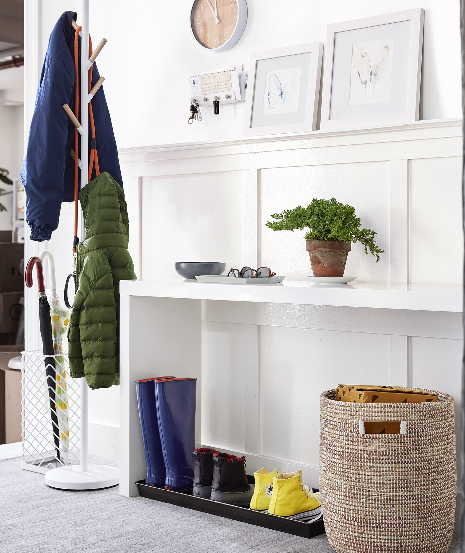 White entryway with shelves, art, basket, standing coat rack