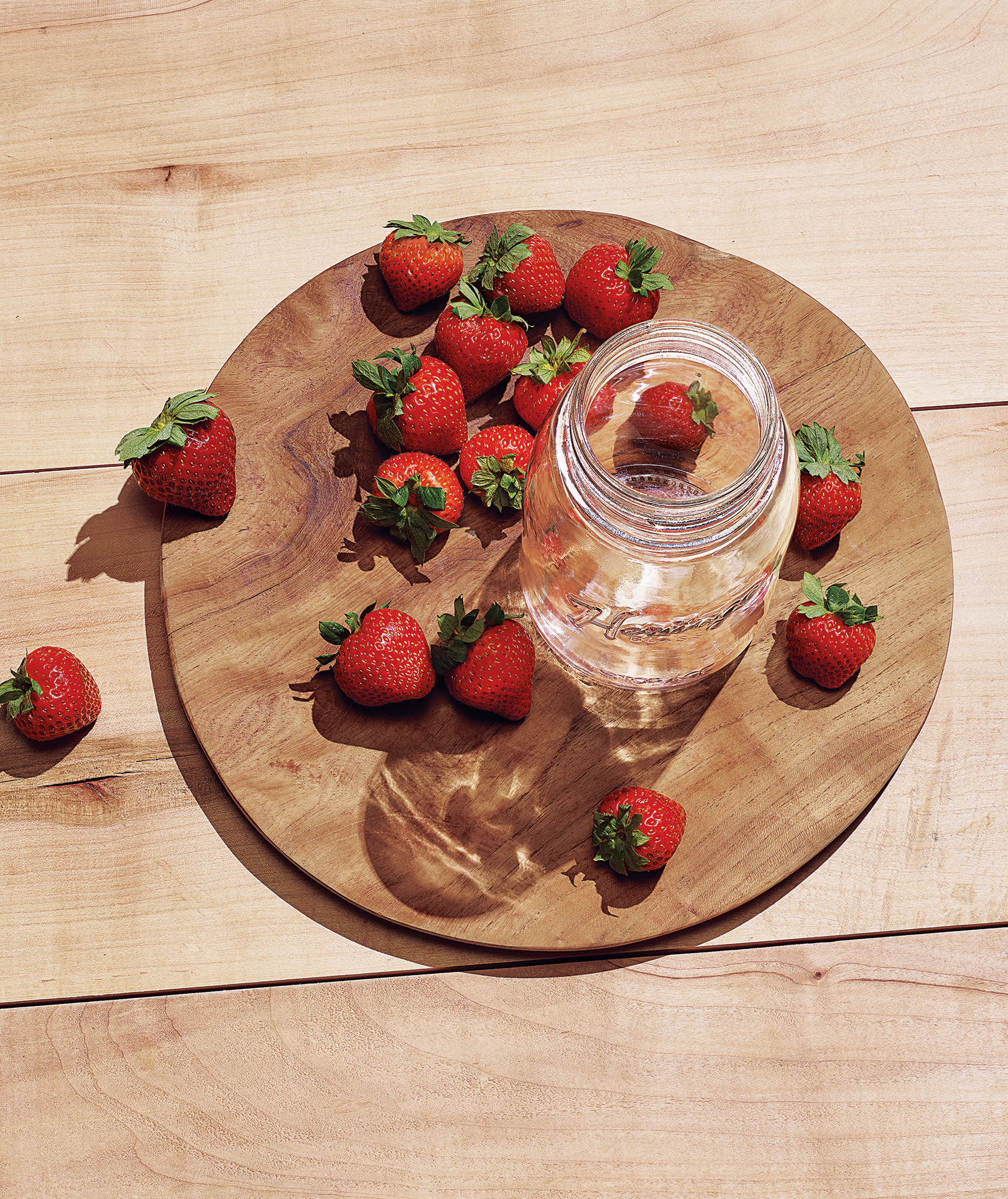 Empty jar and strawberries in sunlight
