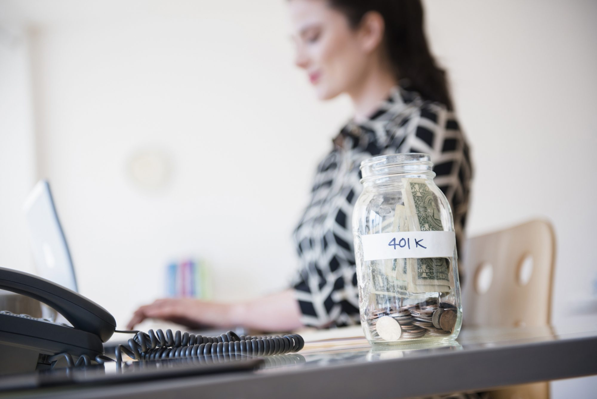 Woman with 401k jar on desk