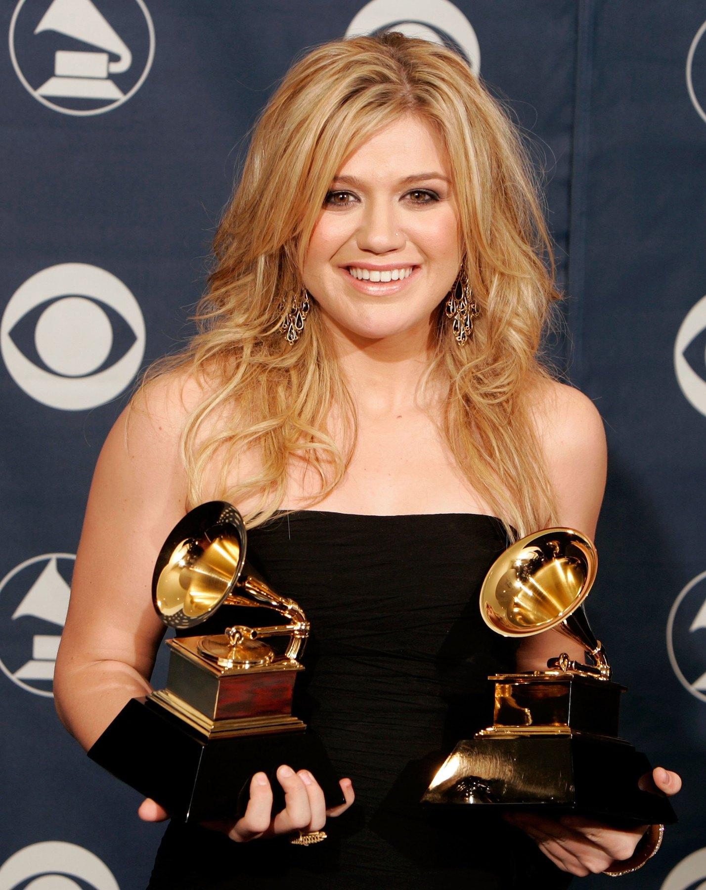 Kelly Clarkson holding two Grammy awards