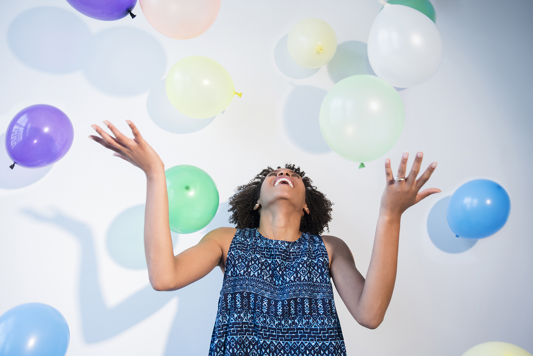 Woman being rained down on by balloons