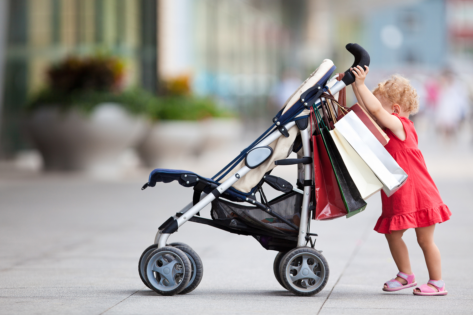 Toddler pushing stroller loaded with shopping bags