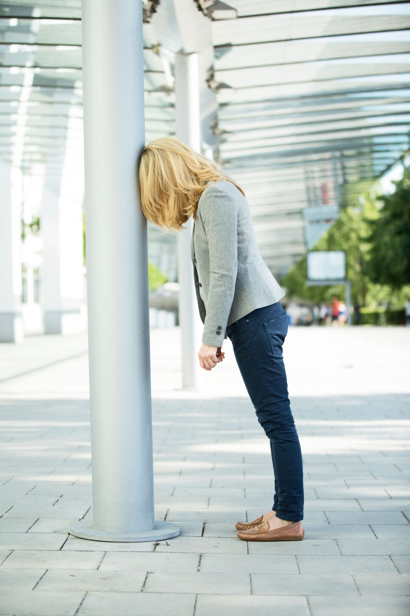 Stressed woman leaning against pole, head down