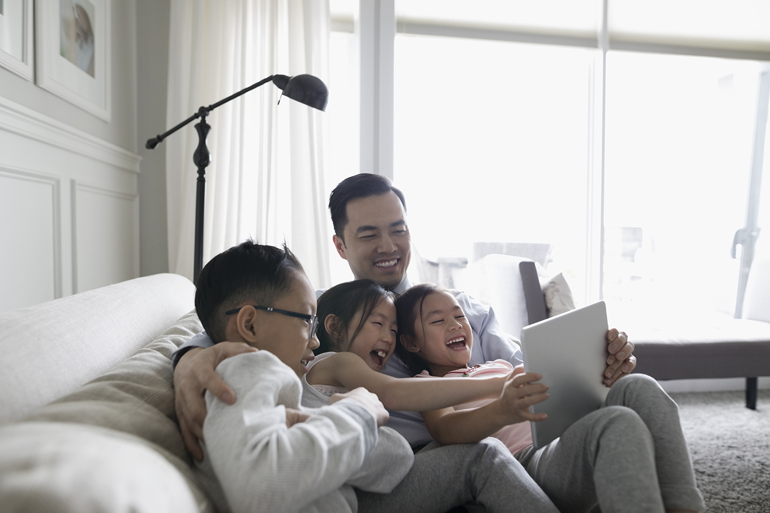 Children and Dad Laughing at Screen