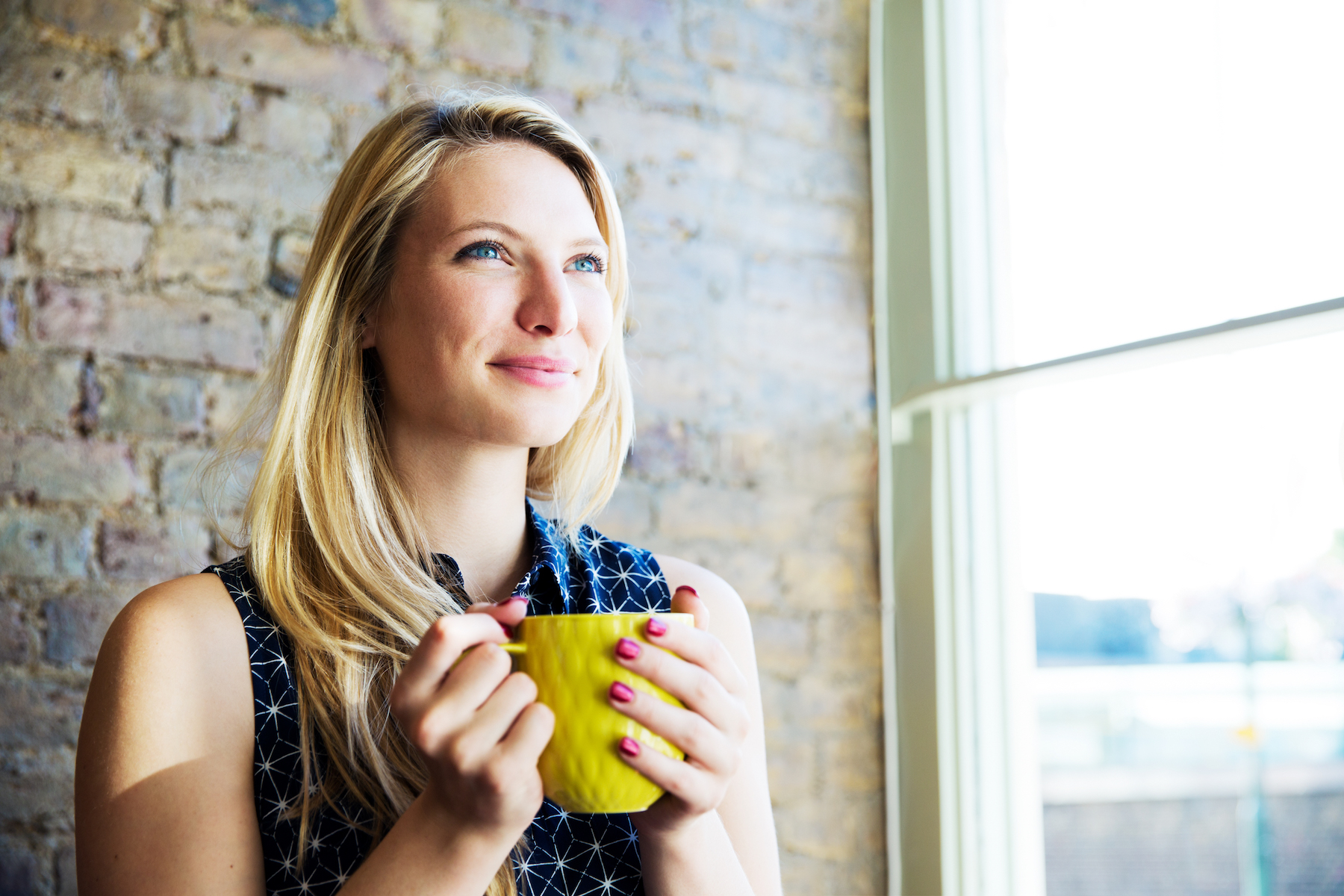 Woman Drinking Coffee by brick wall